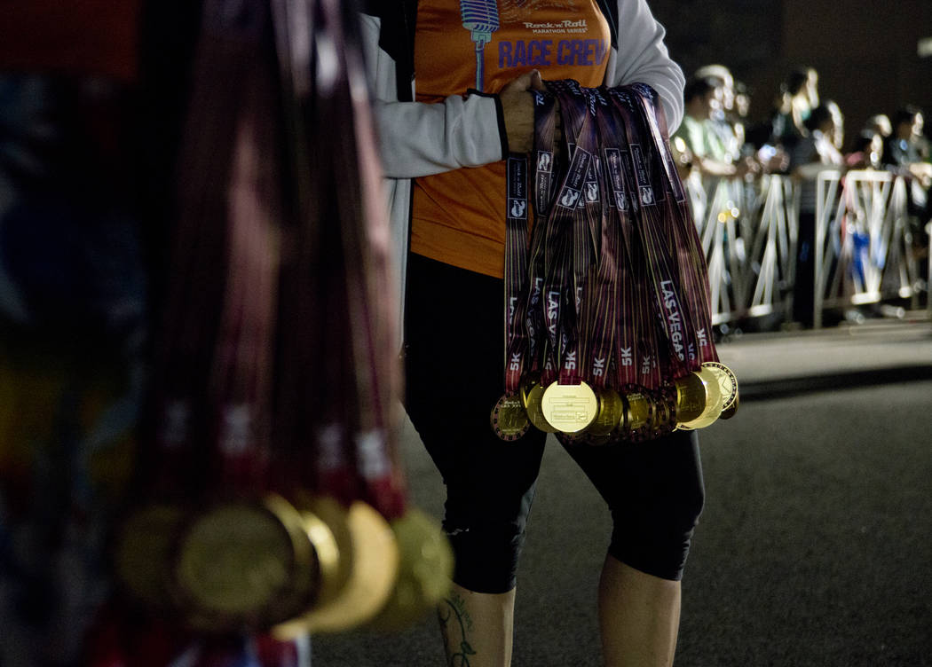Volunteers hold medals to be given out at the end of the 5K portion of the Rock ԮՠRoll Las Vegas Marathon at the Las Vegas Festival Grounds on The Strip on Saturday, Nov. 11, 2017. Dan ...