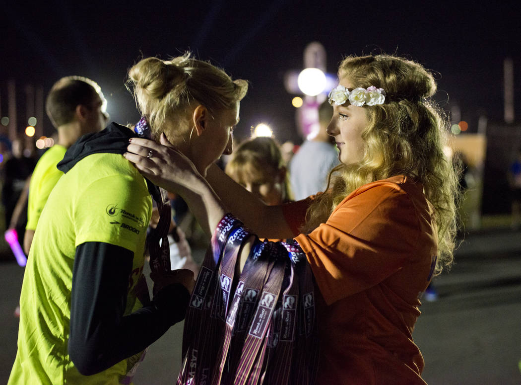 Event volunteer Arita McCabe, right, puts a medal around the neck of Jennifer Watson after the 5K portion of the Rock ԮՠRoll Las Vegas Marathon at the Las Vegas Festival Grounds on The ...