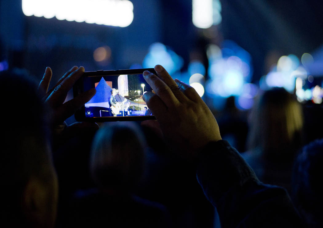 A man takes a photo as the Goo Goo Dolls perform after the 5K portion of the Rock ԮՠRoll Las Vegas Marathon at the Las Vegas Festival Grounds on The Strip on Saturday, Nov. 11, 2017. D ...