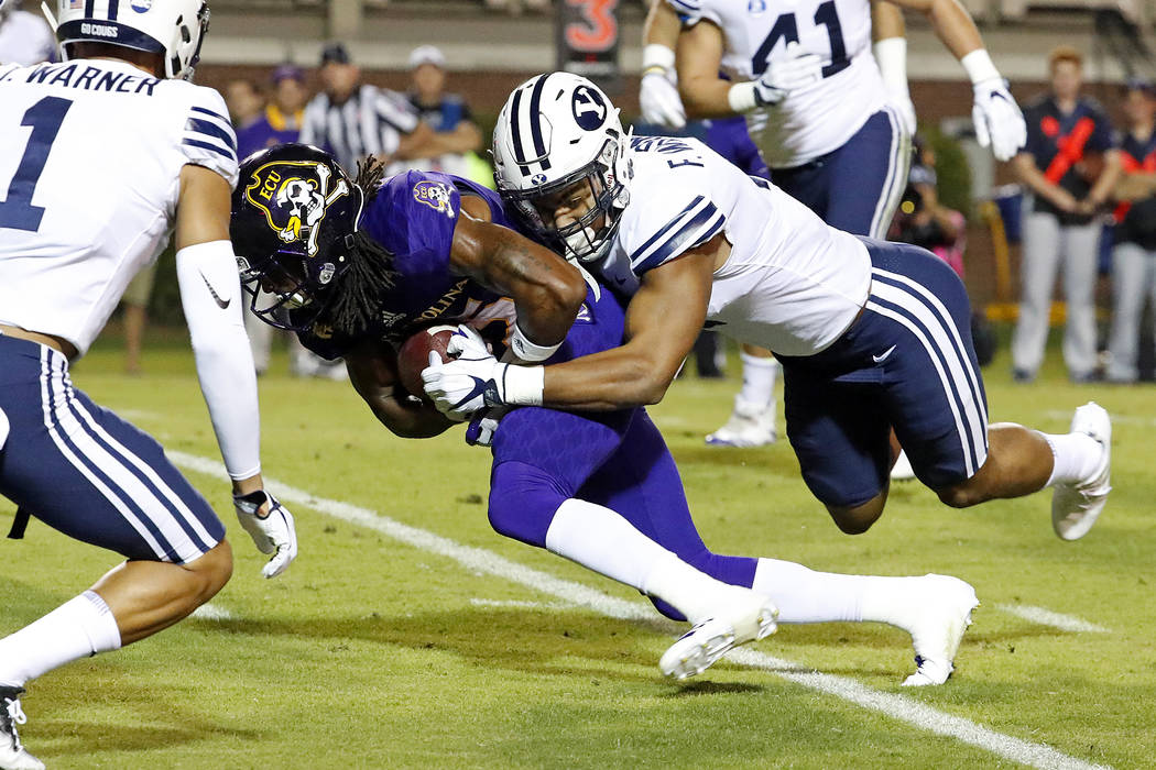 East Carolina's Devin Anderson (25) is pulled down from behind by BYU's Fred Warner (4) during the first half of an NCAA college football game in Greenville, N.C., Saturday, Oct. 21, 2017. (AP Pho ...