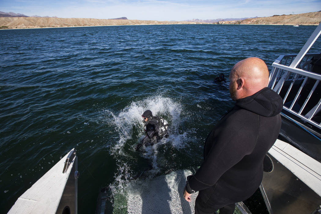 Army and Navy veteran Jeff Pickard, right, watches Army veteran Daniel Gililland dive in the water before the start of submerged resource monitoring demonstration at Lake Mohave in the Lake Mead N ...