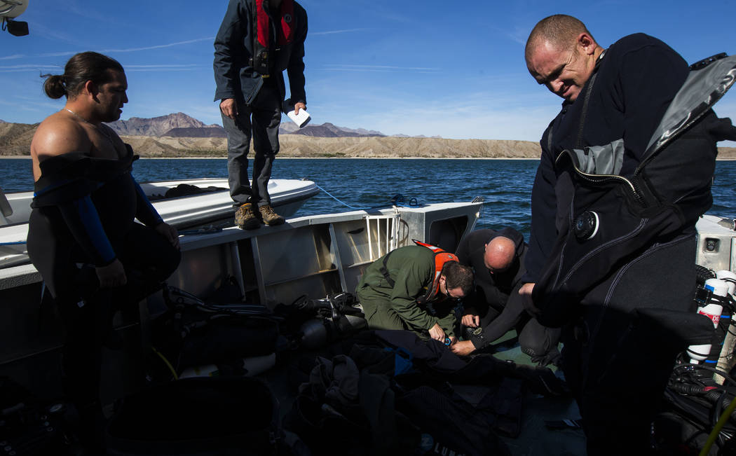Coast Guard veteran Kris Moorehead, left, and Army veteran Daniel Gililland, far right, both members of WAVES, or Wounded American Veterans Experience Scuba, a nonprofit group that promotes scuba  ...