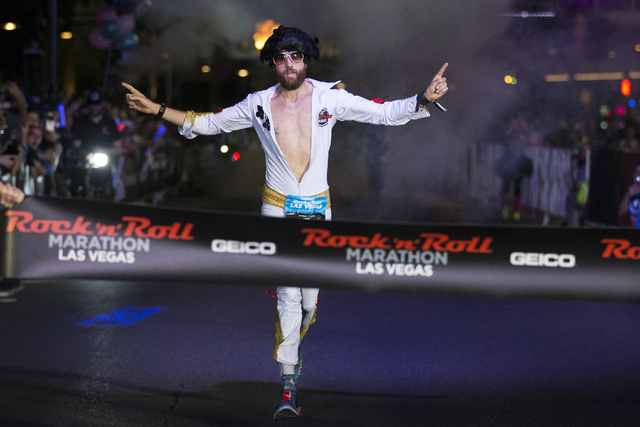 Michael Wardian in costume as Elvis raises his arms in victory as he completes the Rock-n-Roll Marathon for men in first place at the Strip near The Mirage hotel-casino on Sunday, Nov. 13, 2016, i ...