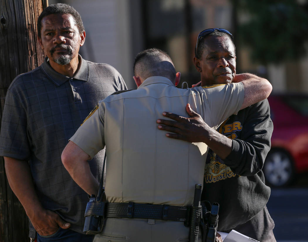 LVMPD Captain Andrew Walsh, center, hugs Larry Winslow, right, husband of Shelia Hawkins who was severely beaten on Nov. 1, as Hawkins' brother Darryl Hawkins, left, stands nearby during a media b ...