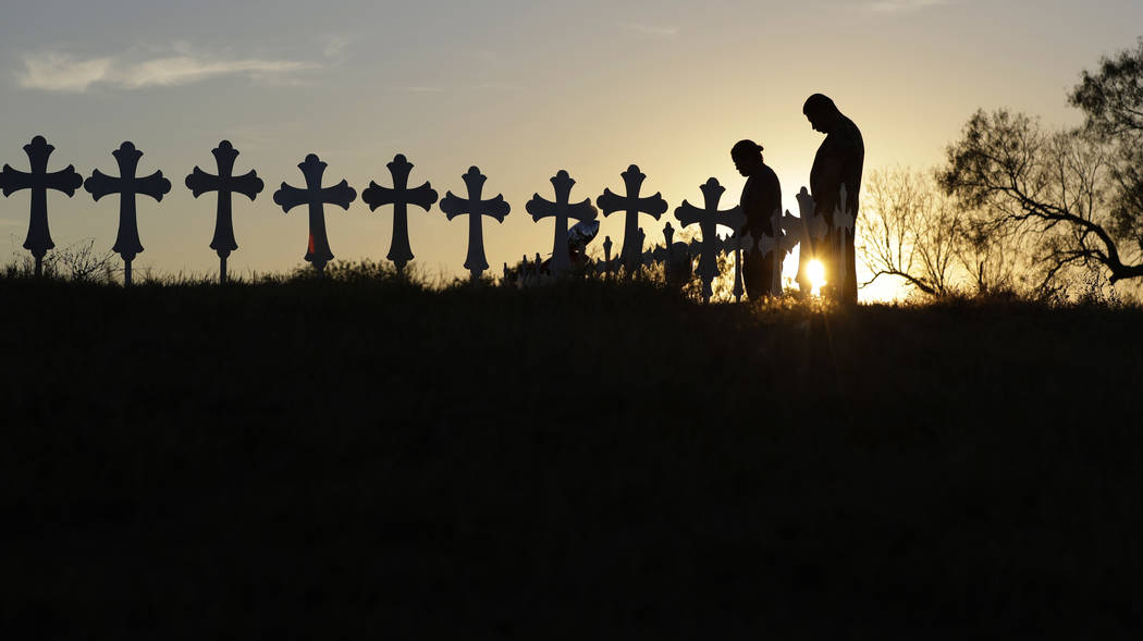 Kenneth and Irene Hernandez pay their respects as they visit a makeshift memorial with crosses placed near the scene of a shooting at the First Baptist Church of Sutherland Springs, Monday, Nov. 6 ...