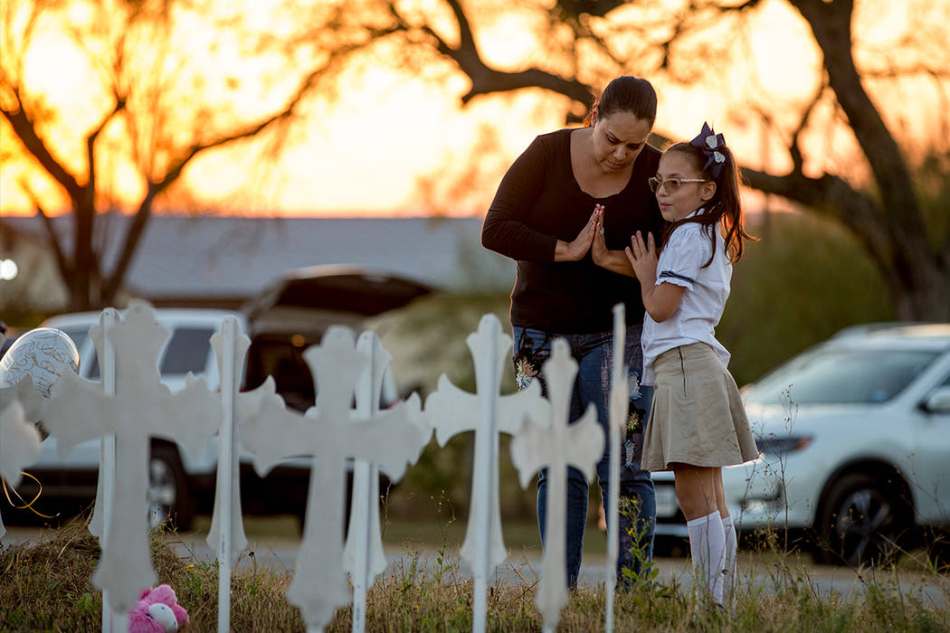 Meredith Cooper, of San Antonio, Texas, and her 8-year-old daughter, Heather, visit a memorial of 26 metal crosses near First Baptist Church in Sutherland Springs, Texas, Monday Nov. 6, 2017. The  ...