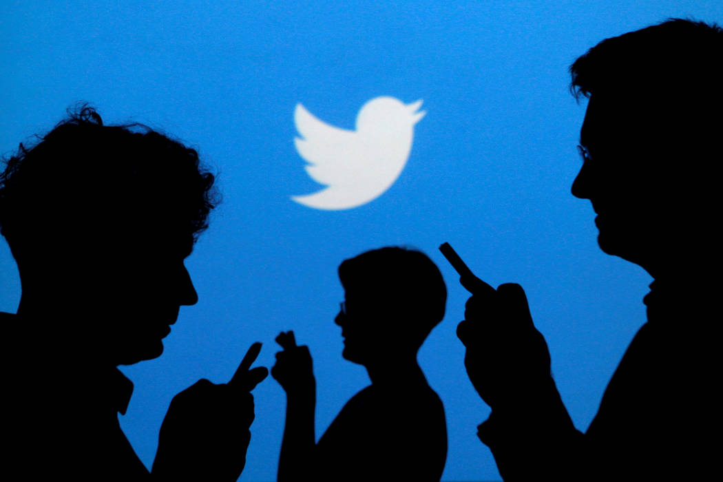 People holding mobile phones are silhouetted against a backdrop projected with the Twitter logo in this illustration picture taken in  Warsaw  on September 27, 2013. (Kacper Pempel/Reuters)