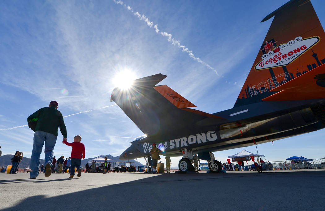Gerald Bonner, 65, who spent 27 years in the United States Air Force, holds the hand of his two-and-a-half-year-old Grandson Dylan Bonner as they walk past the F-15 painted in remembrance of the R ...