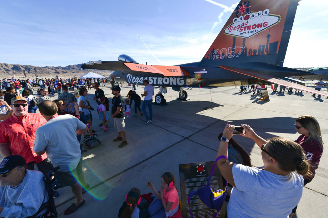 People gather around the F-15C painted in remembrance of the Route 91 mass shooting, some to find shade and others to take photos, during Aviation Nation 2017 at Nellis Air Force Base in Las Vegas ...