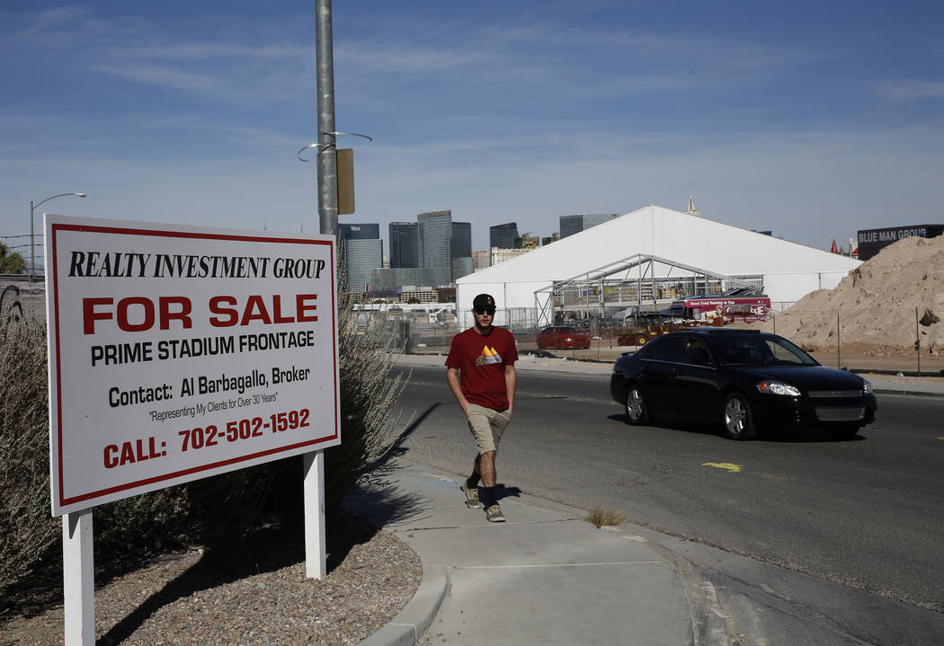 A man walks past a for sale sign outside a property across the street from the Raiders stadium site at the corner of Polaris Avenue and Russel Road Wednesday, Nov. 8, 2017, in Las Vegas. Bizuayehu ...