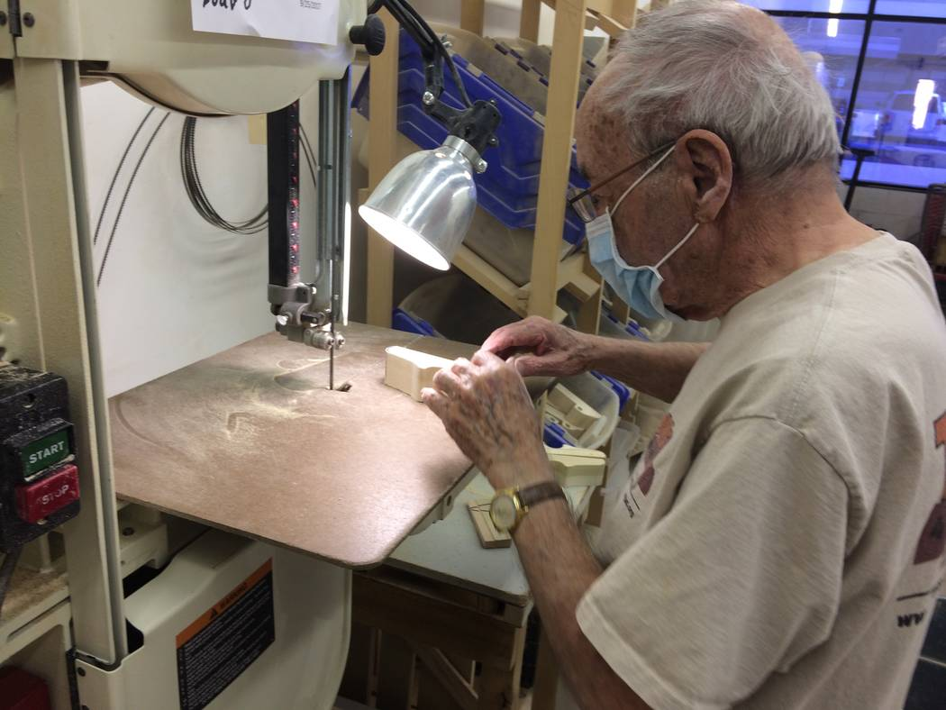 Dan Cooper, 92, works a band saw as he cuts a block of wood to begin making a toy vehicle Oct. 23, 2017, at Toys 4 Smiles. Money is always tight and donations go to pay rent and buy materials such ...