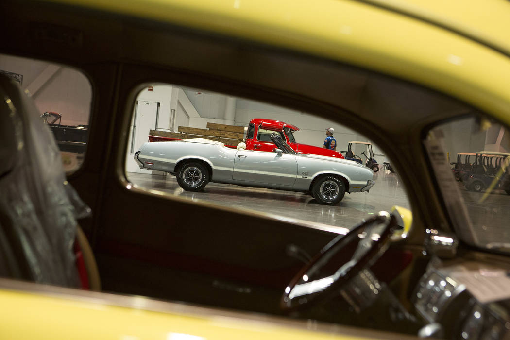 A 1971 Oldsmobile Convertible, seen through a window of another car, is staged in preparation for the Mecum Auction, a live auction of collector and classic cars, at Las Vegas Convention Center in ...