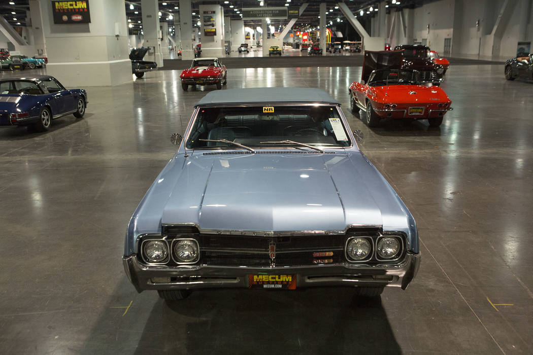 A 1966 Oldsmobile Convertible and other cars are staged in preparation for the Mecum Auction, a live auction of collector and classic cars, at Las Vegas Convention Center in Las Vegas on Tuesday,  ...