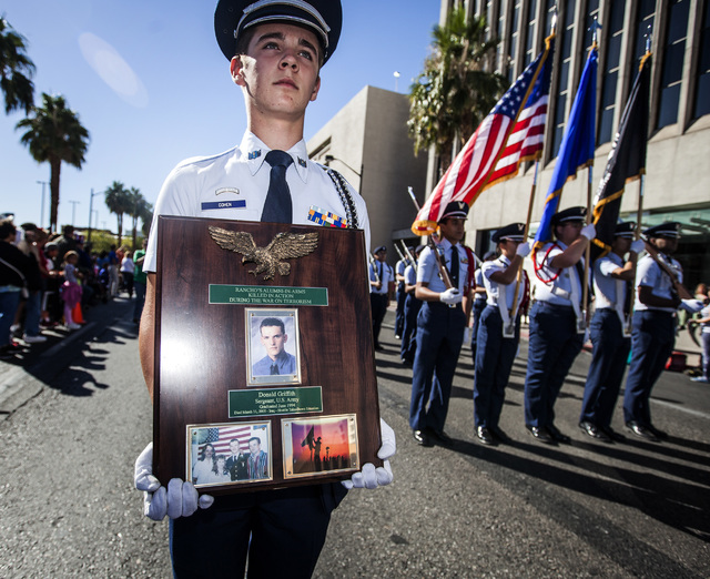 Blaise Cohen,15, with Rancho High School ROTC carries a plaque honoring former student Donald Griffith during the Veteran's Day Parade in downtown Las Vegas on Tuesday, Nov.11, 2014. Griffith grad ...