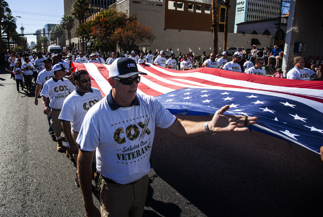 "Jim Ellis carries the American flag  during the Veteran's Day Parade in downtown Las Vegas on Tuesday, Nov.11, 2014. Organizers claim it's the ""largest Veteran's Day parade west of the Mi ..."