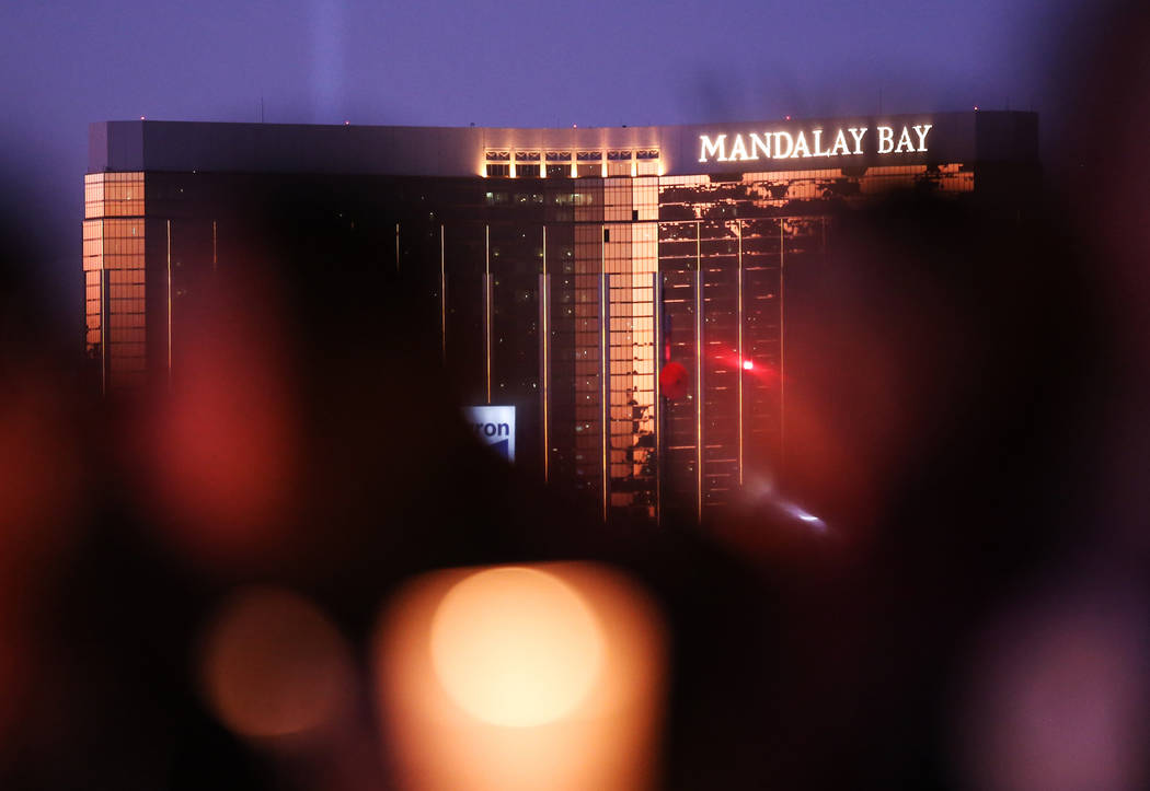 The Mandalay Bay is seen in the distance during a vigil near the Town Square Las Vegas in remembrance of the Mandalay Bay shooting victims in Las Vegas, Monday, Oct. 2, 2017. The shooting took pla ...