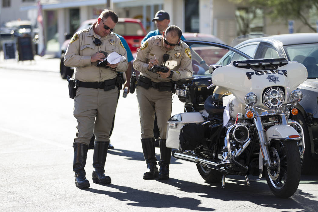Las Vegas police officers at the scene of an accident between a truck and a driverless electric shuttle near Fremont Street and S. 6th Street in Las Vegas during the launch day of the autonomous v ...