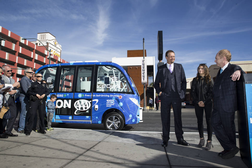 NASCAR driver Danica Patrick, center, with magicians Penn Jillette, left, and Raymond Teller of Penn and Teller, during the launch event of a driverless electric shuttle at the Container Park in L ...