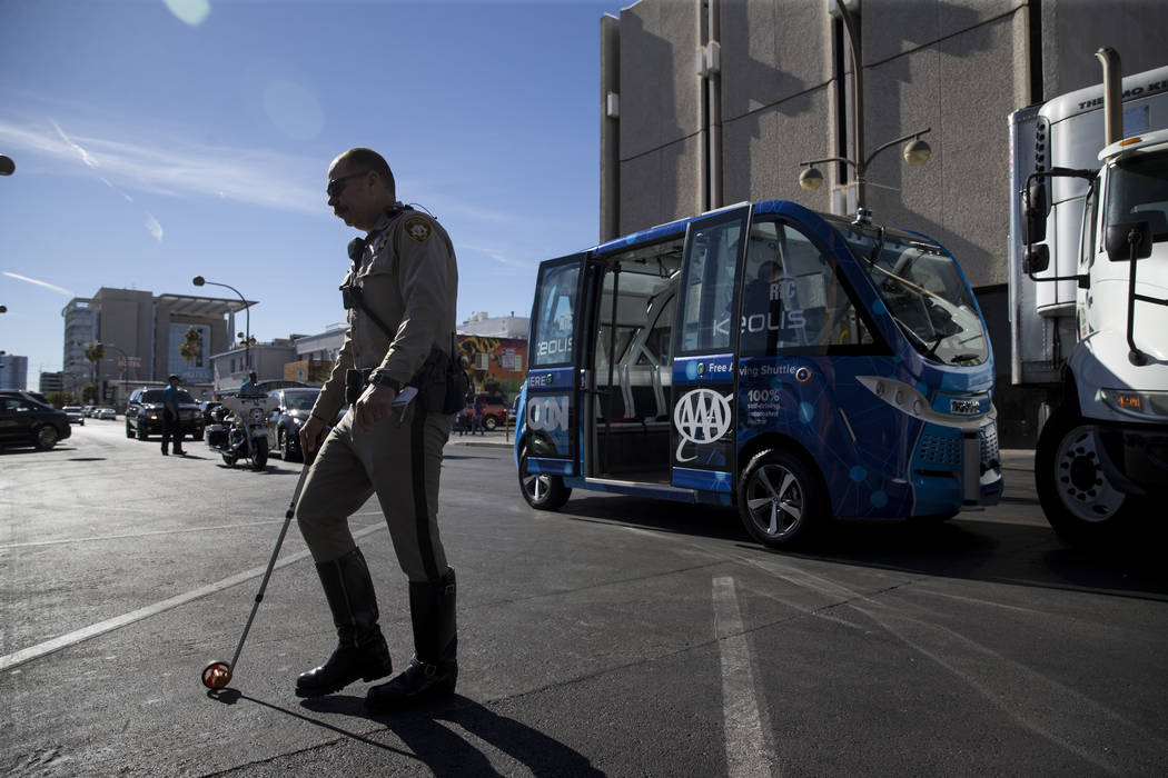 A Las Vegas police officer at the scene of an accident between a truck and a driverless electric shuttle near Fremont Street and S. 6th Street in Las Vegas during the launch day of the autonomous  ...