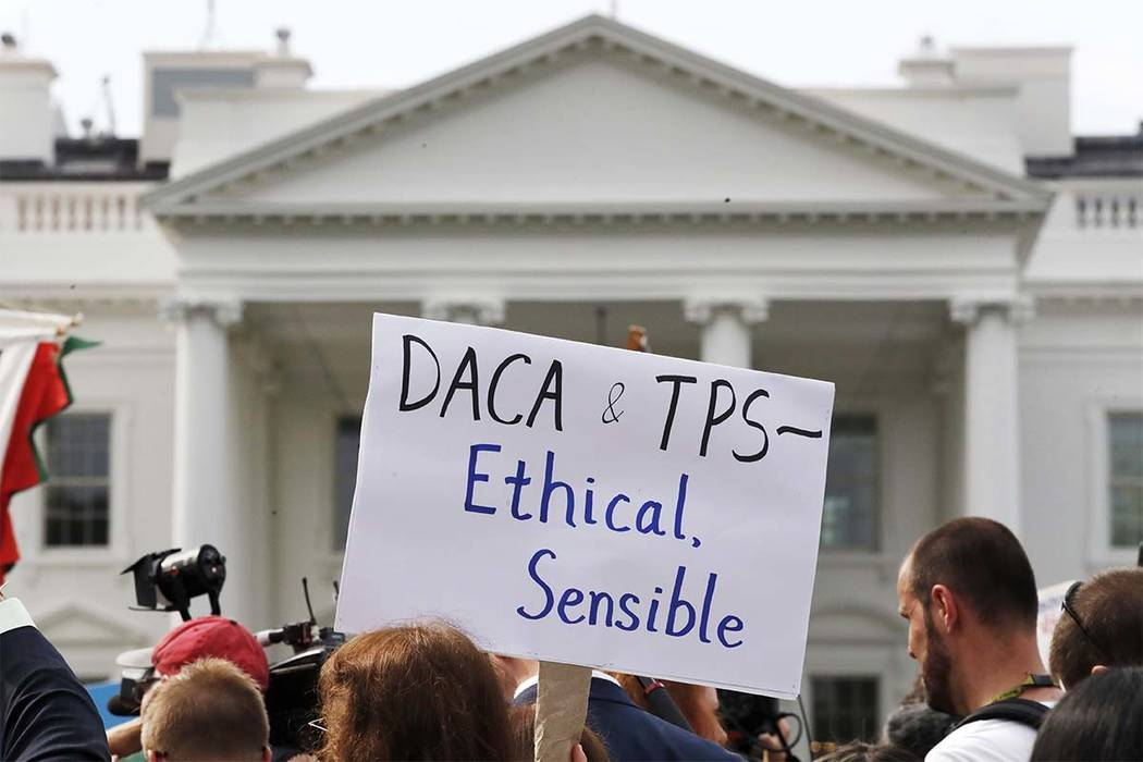 A person holds up a sign in support of the Deferred Action for Childhood Arrivals, known as DACA, and Temporary Protected Status programs during a rally in support of DACA and TPS outside of the W ...