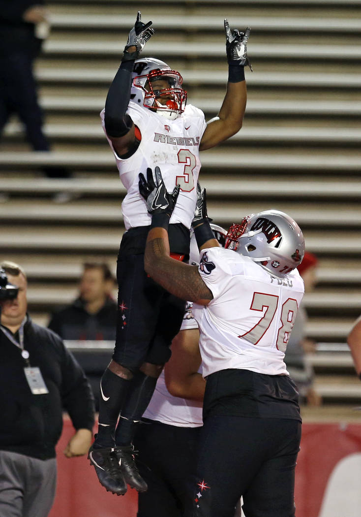 UNLV running back Lexington Thomas (3) celebrates with offensive lineman Justin Polu (78) after scoring a touchdown against New Mexico during the first half of an NCAA college football game in Alb ...