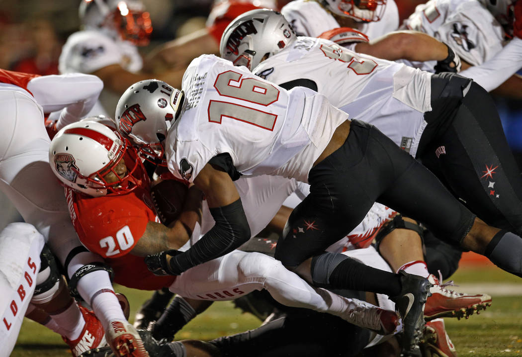New Mexico running back Daryl Chestnut (20) scores a touchdown against the defense of UNLV linebacker Javin White (16) and defensive lineman Nick Dehdashtian (98) during the first half of an NCAA  ...
