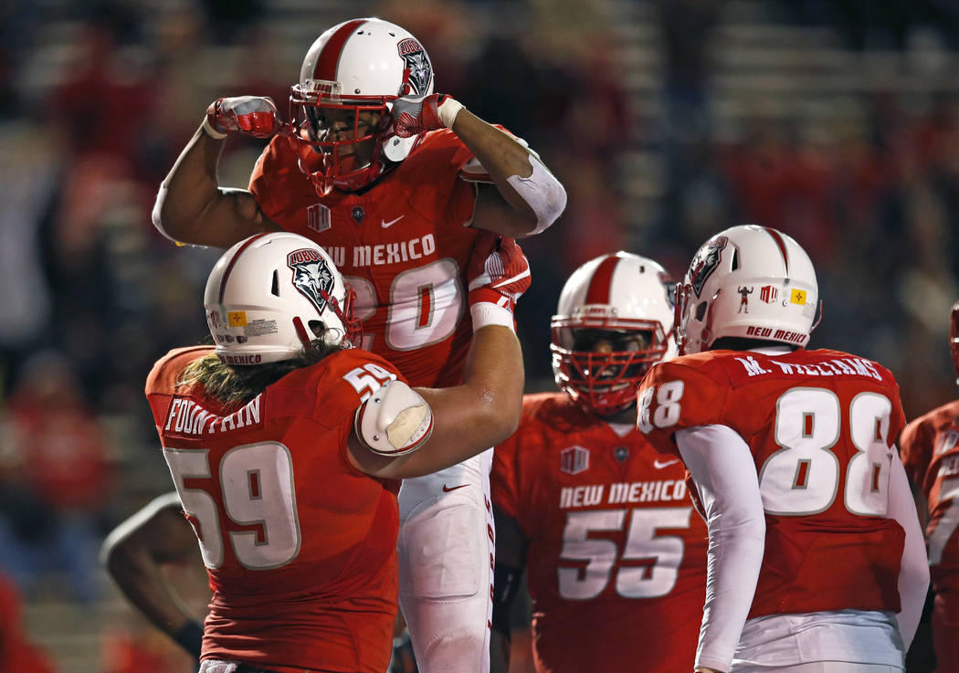 New Mexico running back Daryl Chestnut (20) celebrates with teammate Blaise Fountain (59) after scoring a touchdown against UNLV during the first half of an NCAA college football game in Albuquerq ...