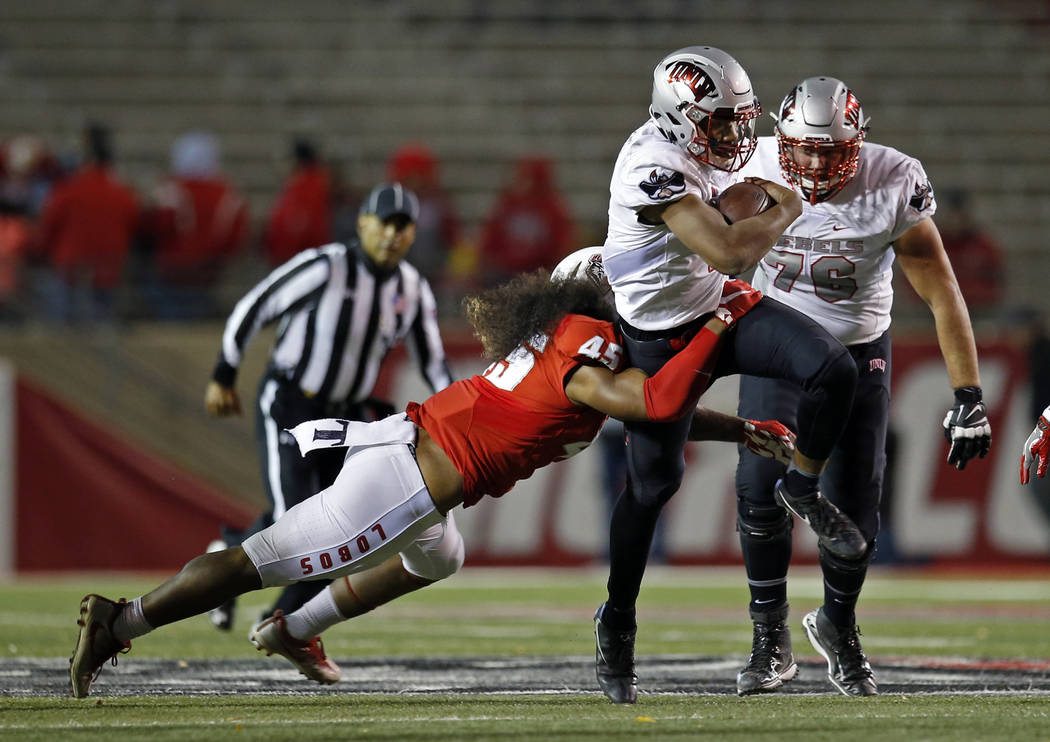 UNLV quarterback Armani Rogers is stopped by New Mexico linebacker Evahelotu Tohi (45) during the first half of an NCAA college football game in Albuquerque, N.M., Friday, Nov. 17, 2017. (AP Photo ...