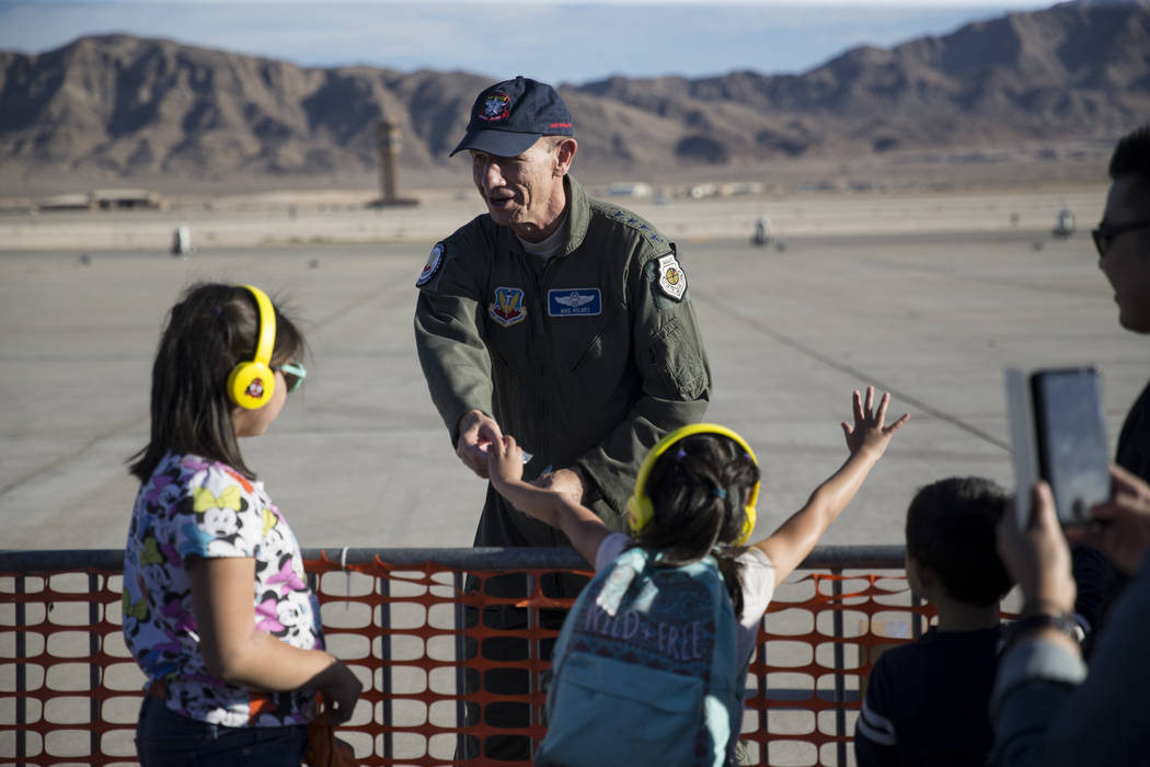 """Gen. James M. """"Mike"""" Holmes, commander for the Air Combat Command, Langley Air Force Base, Virginia, hands out pins during Aviation Nation at Nellis Air Force Base in Las Vegas,  ..."""