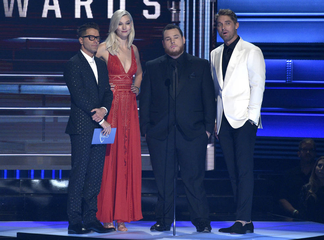 Bobby Bones, from left, Karlie Kloss, Luke Combs and Brett Young present the award for song of the year at the 51st annual CMA Awards at the Bridgestone Arena on Wednesday, Nov. 8, 2017, in Nashvi ...