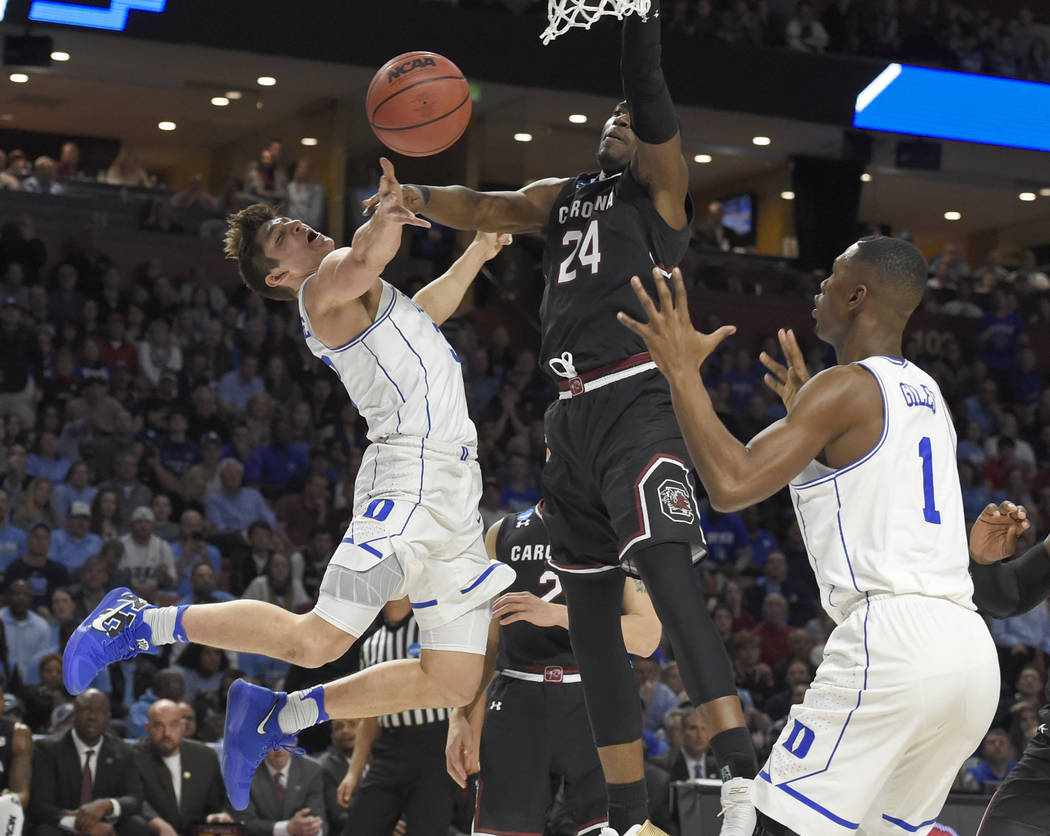 Duke's Grayson Allen, left, is fouled by South Carolina's Sedee Keita, center, as he tries to pass the ball to Harry Giles, right, during the first half in a second-round game of the NCAA men's co ...