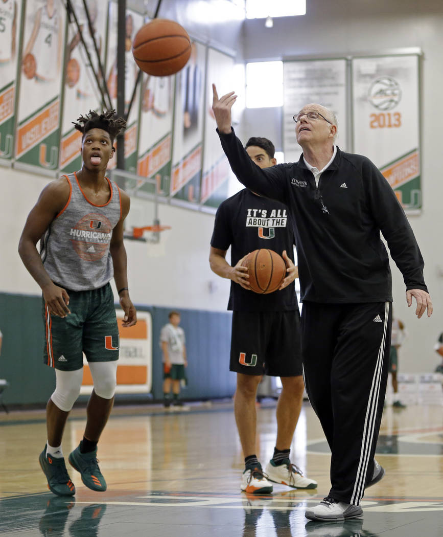 Miami head coach Jim Larranaga, right, tosses the ball as Lonnie Walker, left, looks on, Monday, Oct. 23, 2017, during an NCAA basketball media day practice, in Coral Gables, Fla. (AP Photo/Alan Diaz)