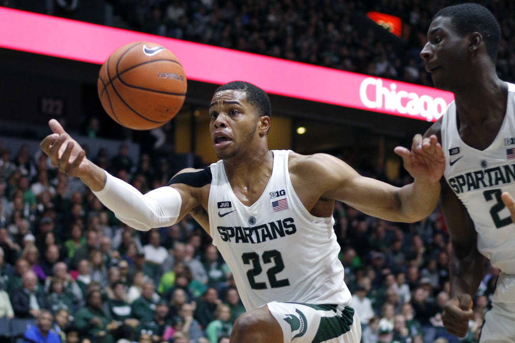 FILE - In this Oct. 29, 2017, file photo, Michigan State's Miles Bridges (22) pulls in the ball as Jaren Jackson Jr. (2) watches during the first half of an NCAA college basketball exhibition game ...