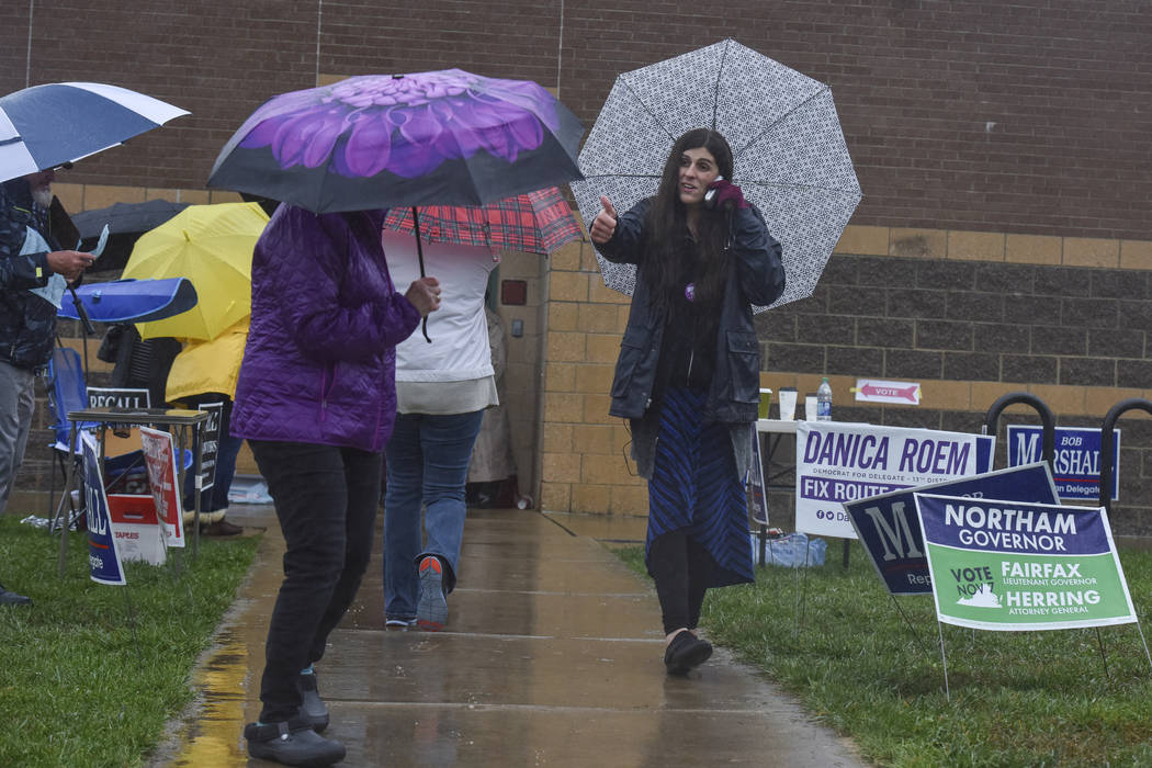 Danica Roem, right, who defeated GOP incumbent Robert Marshall for a seat in the Virginia house of delegates, campaigns as voters take to the ballot boxes at Gainesville Middle School on Tuesday,  ...