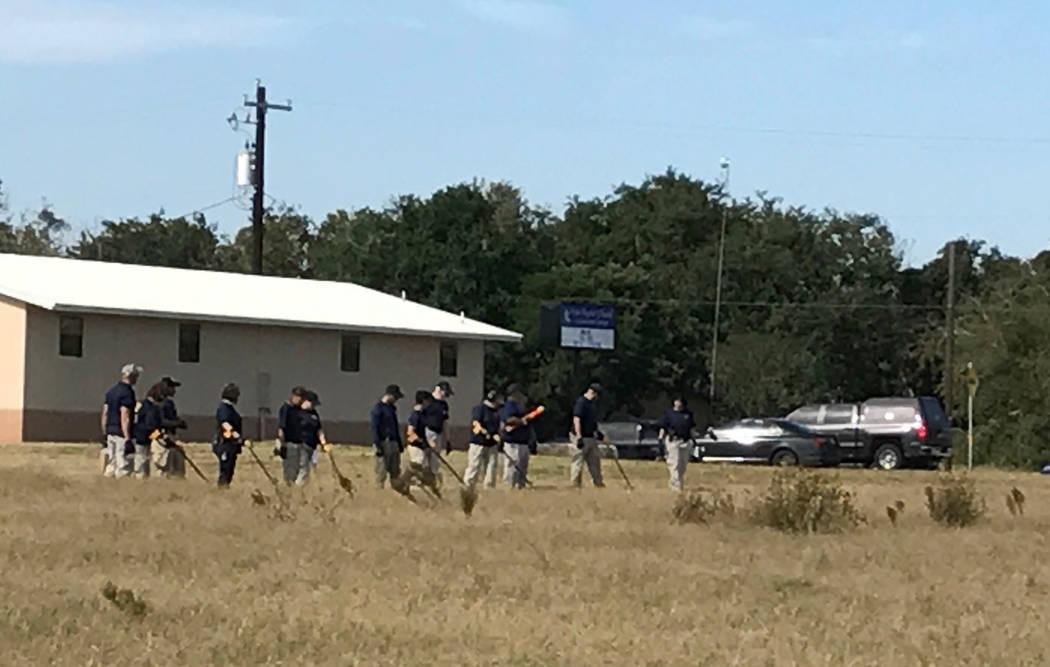 Los agentes del FBI usan detectores de metales en busca de evidencia cerca de la iglesia en Sutherland Springs, Texas. Foto de Gary Martin