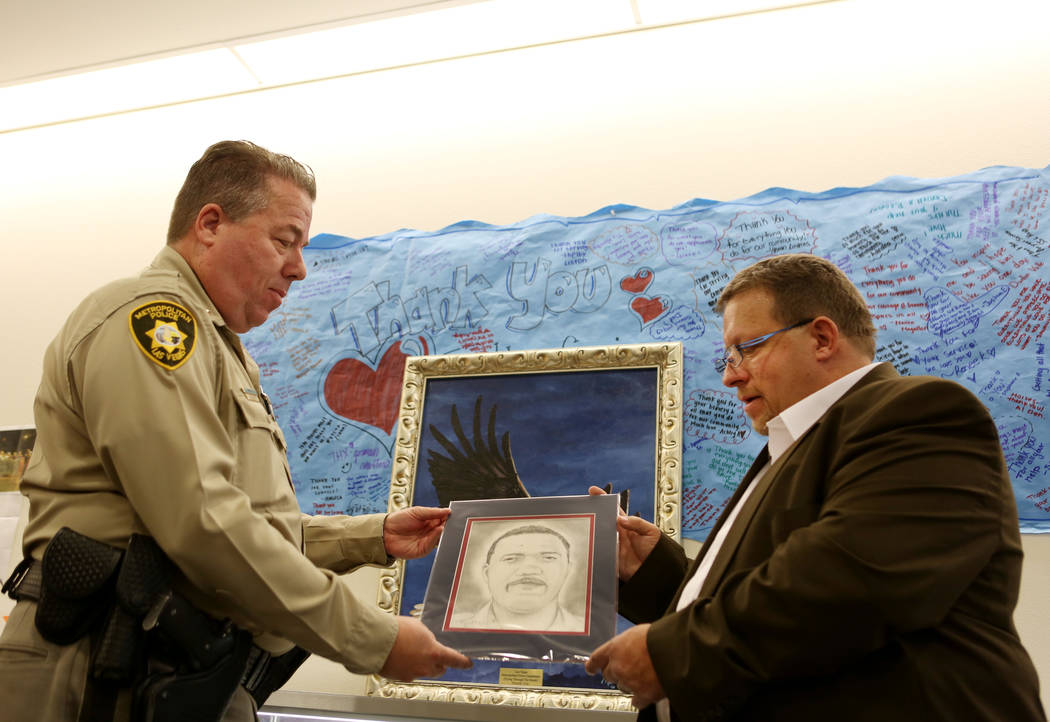Metropolitan Police Deputy Chief John McGrath, left, and Ohio-based artist Ron Moore Jr. hold Moore's portrait of Charleston Hartfield at Metro headquarters in Las Vegas, Tuesday, Nov. 14, 2017. H ...