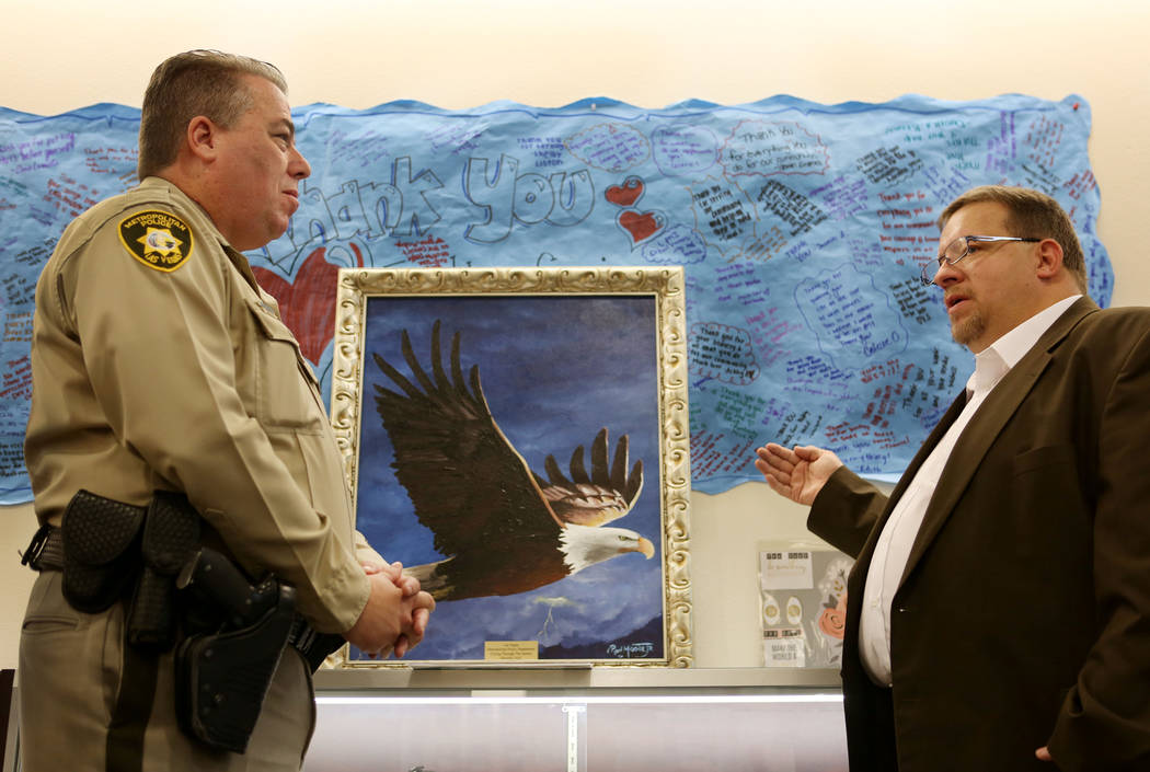 Metropolitan Police Deputy Chief John McGrath, left, listens to Ohio-based artist Ron Moore Jr. explain his painting of an eagle at Metro headquarters in Las Vegas, Tuesday, Nov. 14, 2017. Moore g ...