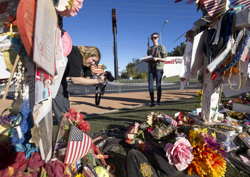 Clark County Museum Registrar Cynthia Sanford, left, and intern Meghan Romane photograph and document the crosses and mementos left at a memorial for Route 91 Harvest shooting victims at the Welco ...