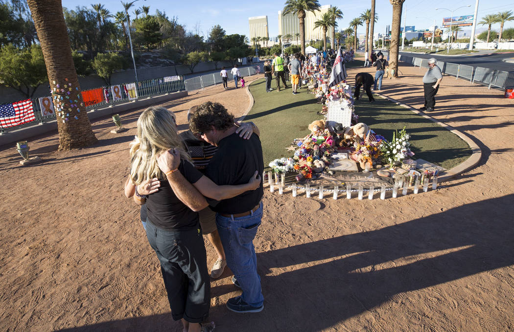 Route 91 Harvest shooting survivors Nannette Doyle, left, and Doug Dimitruk of Diamond Bar, California, gather in prayer with friends after visiting a memorial for Route 91 shooting victims at the ...