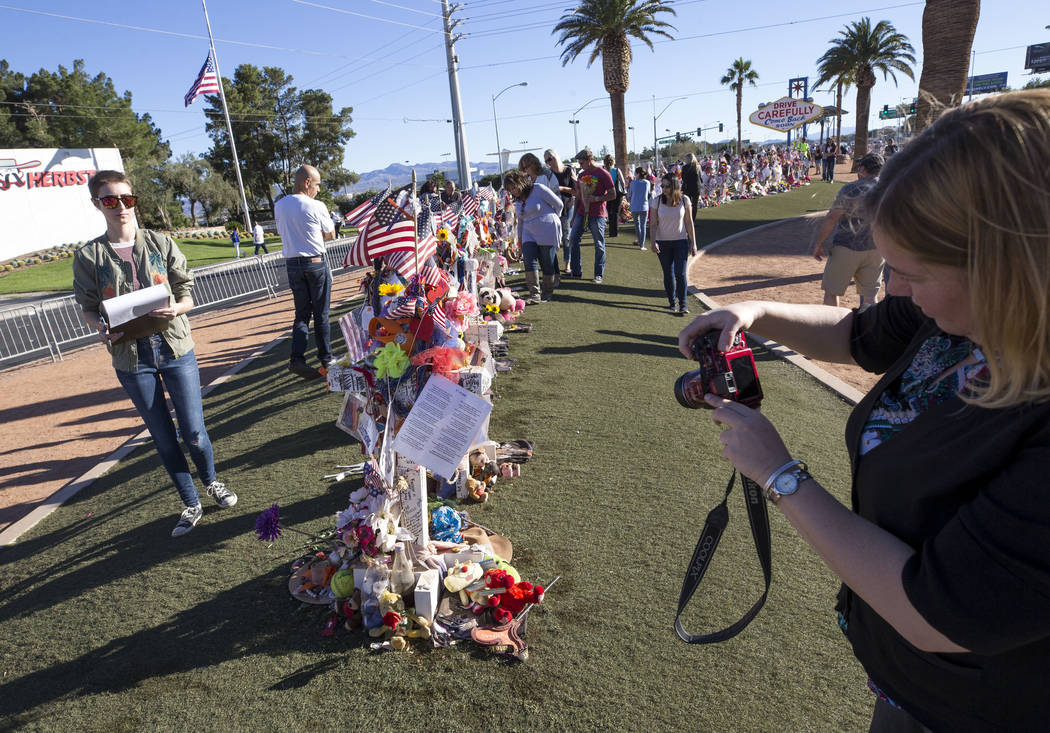 Clark County Museum Registrar Cynthia Sanford, forground, and intern Meghan Romane, left, photograph and document the crosses and mementos left at a memorial for Route 91 Harvest shooting victims  ...