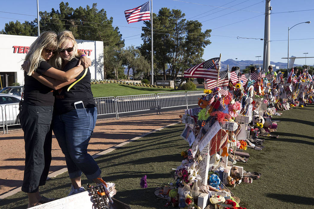 Route 91 Harvest shooting survivors Nannette Doyle, left, and Diana Dimitruk of Diamond Bar, California, comfort each other while visiting a memorial for Route 91 shooting victims at the Welcome t ...
