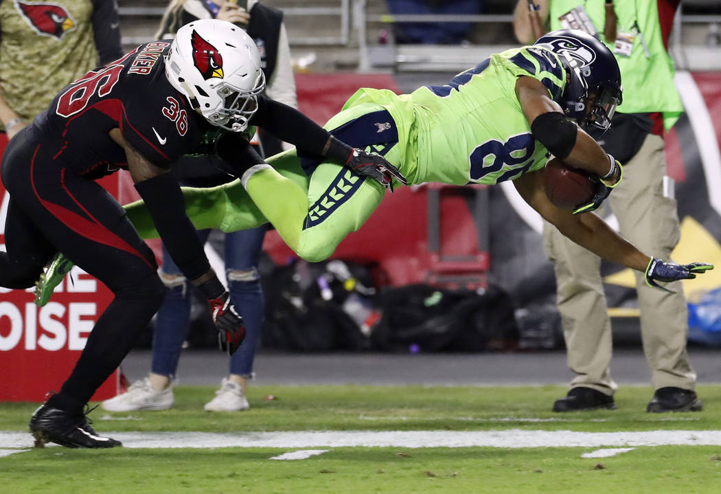 Seattle Seahawks wide receiver Doug Baldwin (89) is hit out of bounds by Arizona Cardinals safety Budda Baker (36) during the second half of an NFL football game, Thursday, Nov. 9, 2017, in Glenda ...
