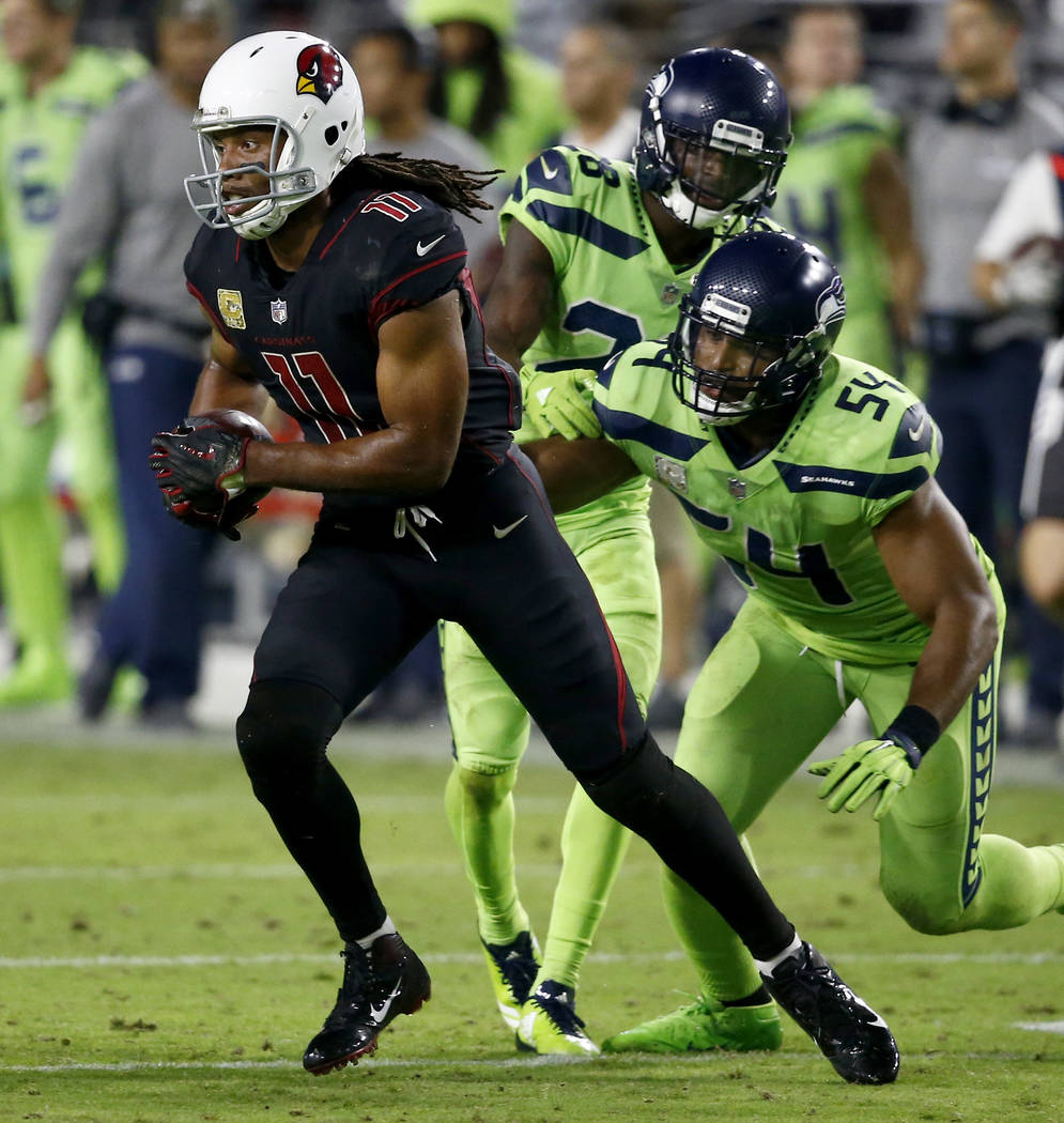 Arizona Cardinals wide receiver Larry Fitzgerald (11) runs after the catch as Seattle Seahawks middle linebacker Bobby Wagner (54) pursues during the second half of an NFL football game, Thursday, ...