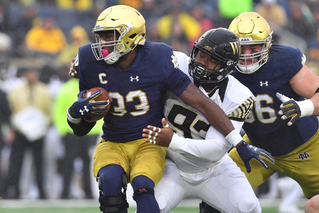 Nov 4, 2017; South Bend, IN, USA; Notre Dame Fighting Irish running back Josh Adams (33) is hit by Wake Forest Demon Deacons defensive tackle Zeek Rodney (93) in the first quarter at Notre Dame St ...