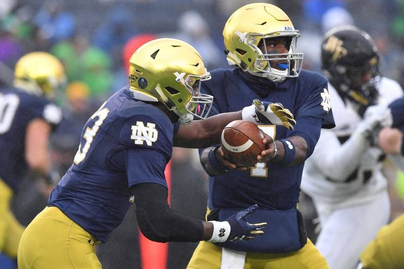 Nov 4, 2017; South Bend, IN, USA; Notre Dame Fighting Irish quarterback Brandon Wimbush (7) hands off to running back Josh Adams (33) in the first quarter against the Wake Forest Demon Deacons at  ...