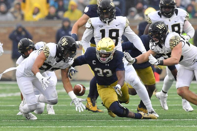 Nov 4, 2017; South Bend, IN, USA; Wake Forest Demon Deacons linebacker Justin Strnad (23) and Notre Dame Fighting Irish running back Josh Adams (33) dive for a loose ball in the second quarter at  ...
