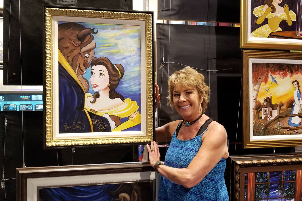 "Paige O'Hara shows off one of her ""Tale as Old as Time"" replicas at Magical Memories Featuring Disney Fine Art in the Forum Shops at Caesars. (Rochelle Richards/Las Vegas Review-Journal)"