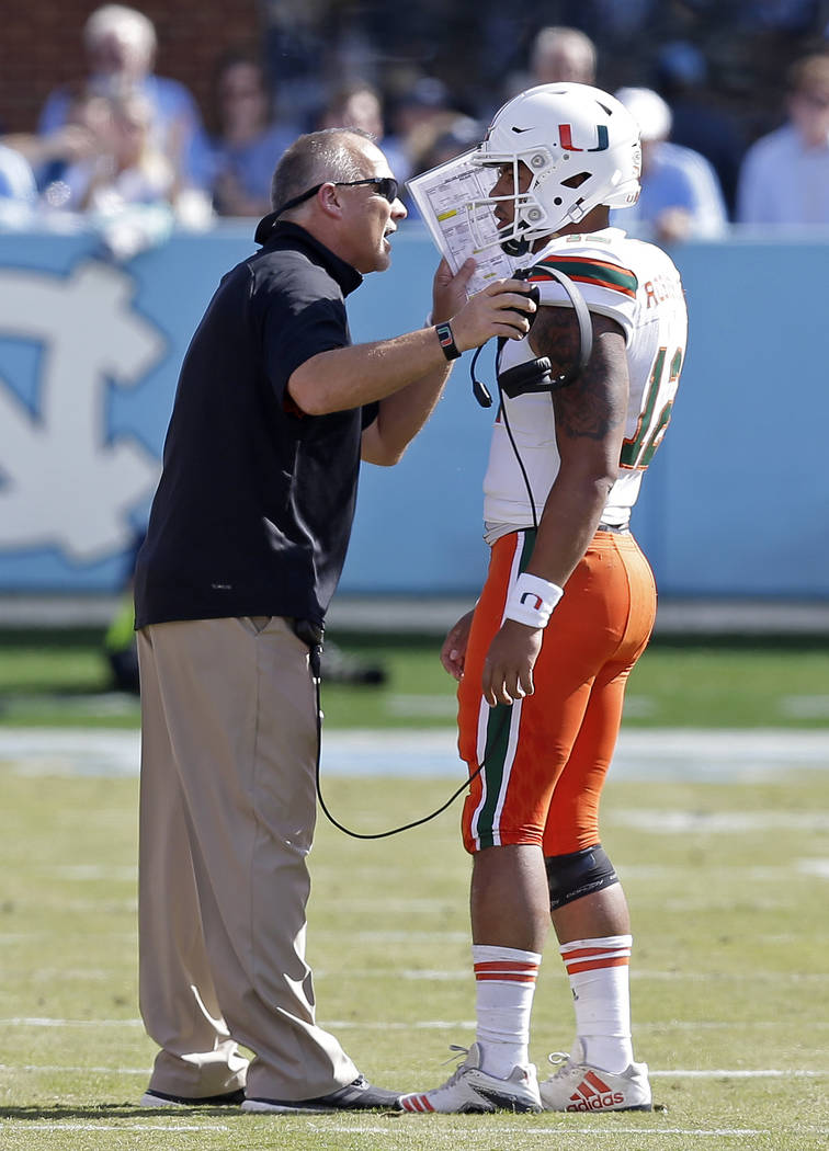 Miami head coach Mark Richt speaks with quarterback Malik Rosier (12) during the first half of an NCAA college football game against North Carolina in Chapel Hill, N.C., Saturday, Oct. 28, 2017. ( ...