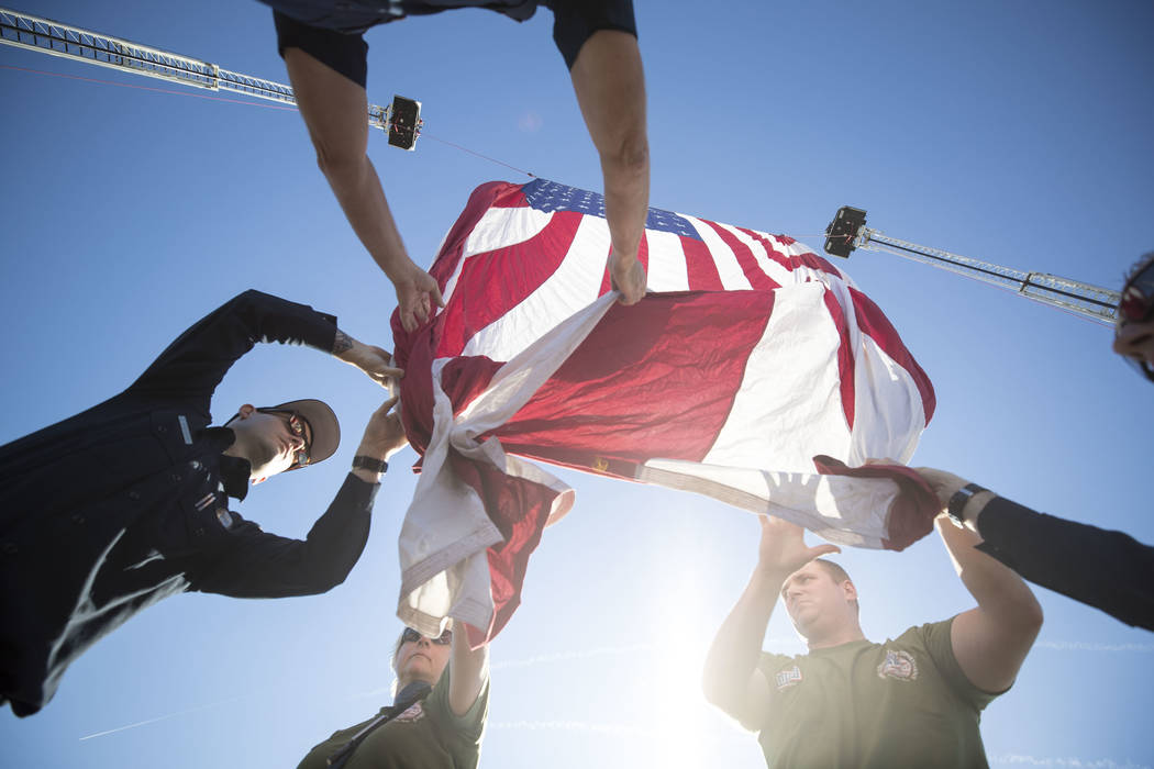 Clark County Fire Department's Zack Schaffer, from left, Annette Simonini, Sean Collins and Matt Turner hang an American Flag from the ladders of two firetrucks ahead of the Project Hero Honor Rid ...