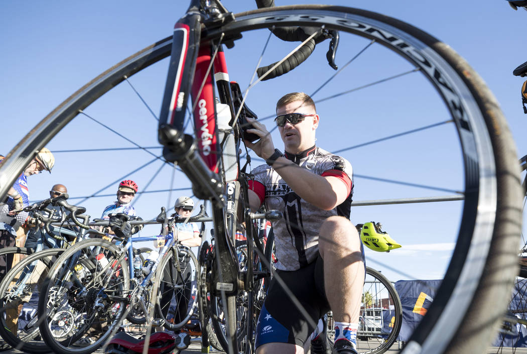 U.S. Marine Kevin Courtney makes an adjustment to his saddle ahead of the Project Hero Honor Ride in Las Vegas, Saturday, Nov. 11, 2017. Over 700 riders participated in the non-competitive race to ...